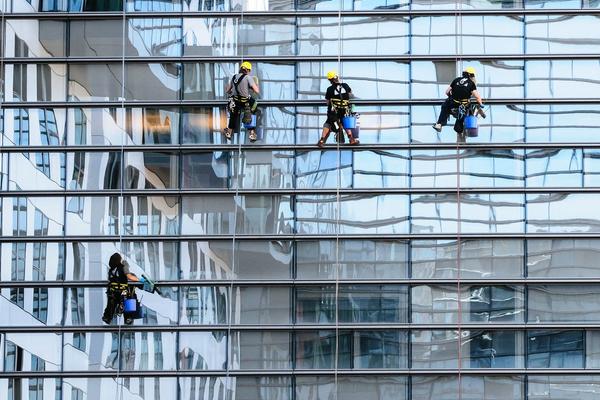 Miehiä rakennustelineillä lasisen pilvenpiirtäjän edessä
