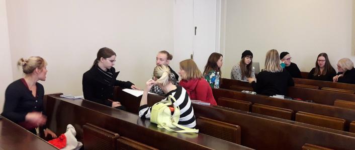 opiskelijat keskustelevat luentosaliss